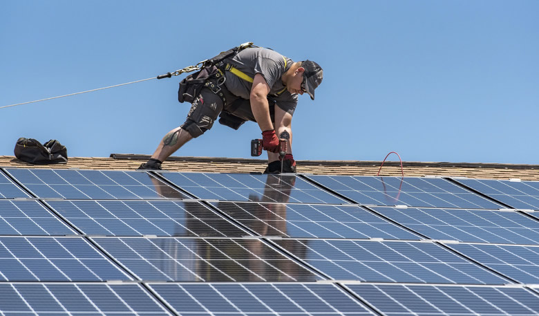 Service member installs solar panels at Dover Air Force Base.